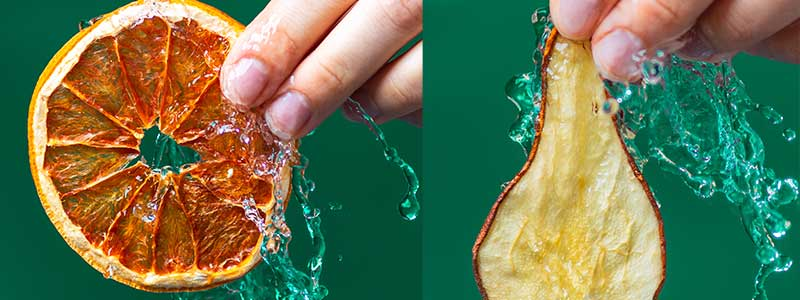 Fruitanicals - Garnishes make a difference - holding up a slice of orange and pear with water splash on a green background